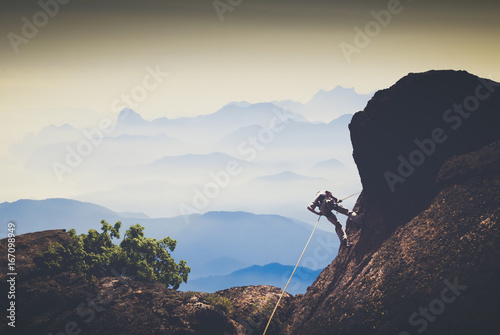 Fotografiet  Climber against mountain valley. Instagram stylization