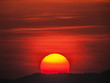 A large, red, setting sun in a red sky, Thailand