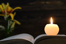 Candle, Opened Book And Flowers  On Dark Wooden Background