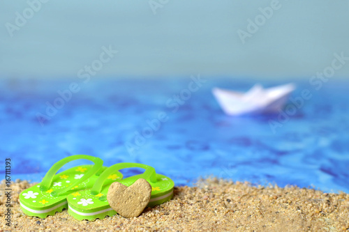 6adf3523ecb5e Summer background with flip flops and heart shaped stone on the sandy beach