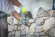 Worker Rides A Stone Wall On A Traditional Renovation Site