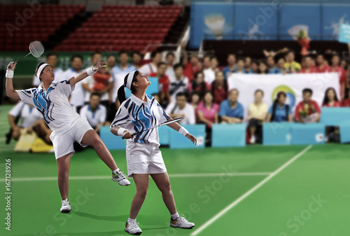 Obrazy Badminton   young-female-players-playing-doubles-with-spectators-in-the-background