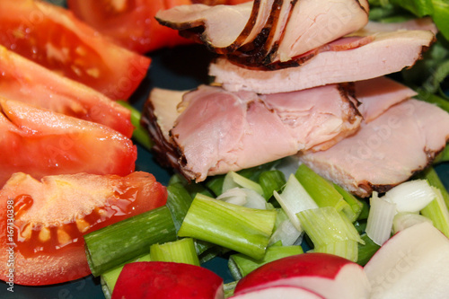 Slice of smoked meat with tomato and radish