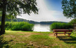 canvas print picture - A small lake in the evening sun with a bench and table in north bohemia