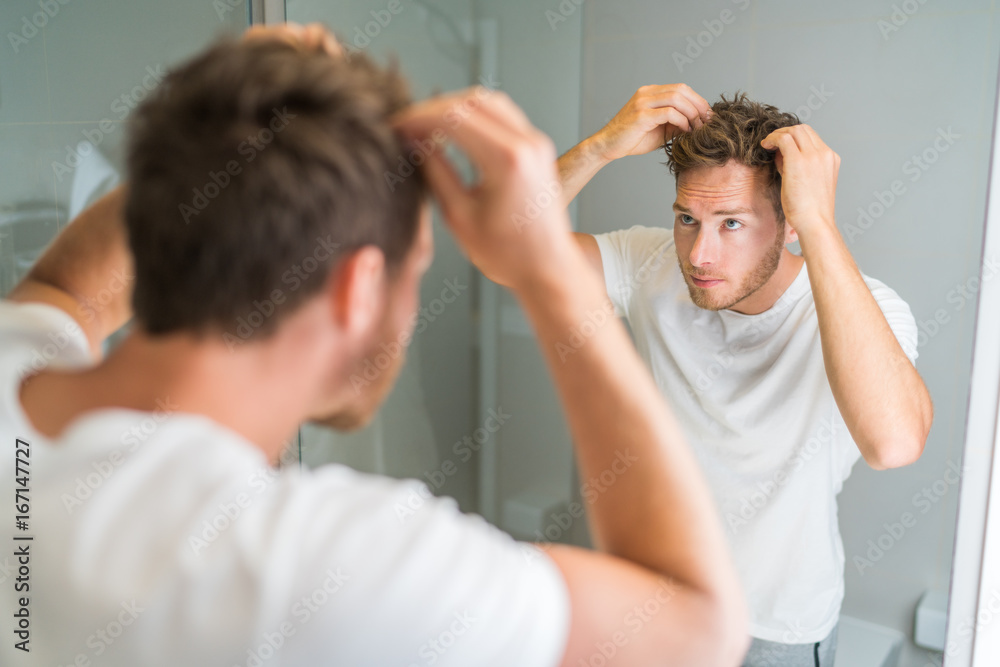 Fototapeta Hair loss man looking in bathroom mirror putting wax touching his hair styling or checking for hair loss problem. Male problem of losing hairs.