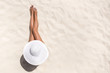 Leinwandbild Motiv Summer holiday fashion concept - tanning woman wearing sun hat at the beach on a white sand shot from above