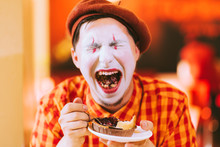 The Clown Is Eating A Cake In ...