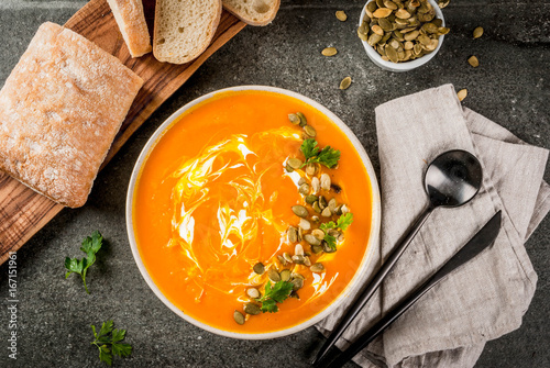 Traditional fall and winter dishes, hot and spicy pumpkin  soup with pumpkin seeds, cream and freshly baked baguette, on black stone table, copy space top view