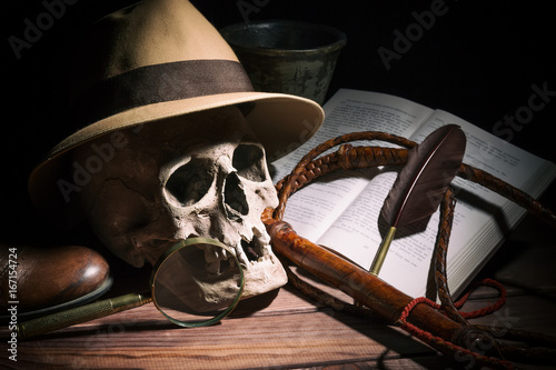 Adventure and archeology concept. Skull with fedora hat, bullwhip, book, quill, shoe, mortyr and magnifying glass on wooden table and black background. Still life.