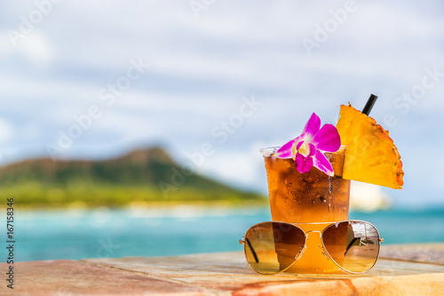 Hawaii mai tai cocktail drink on waikiki beach bar with flower, pineapple and sunglasses. View of the ocean and diamond head mountain in Honolulu, Hawaii. Summer vacation.
