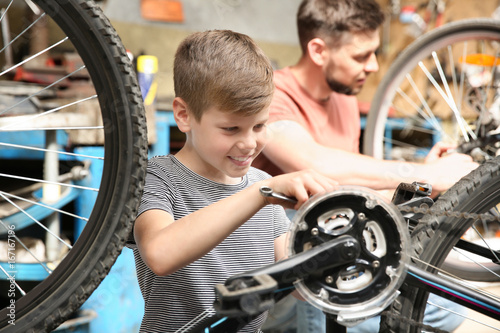 Dad and son fixing bicycles in garage