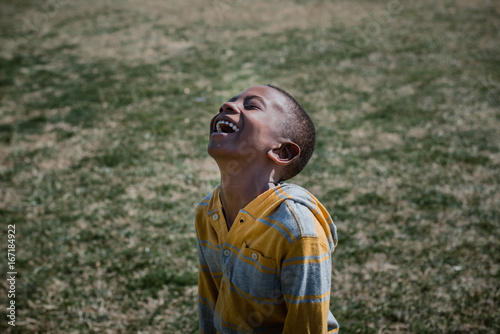 boy with joyful expression laughing outside