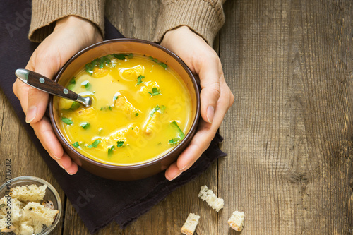 hands holding bowl of soup