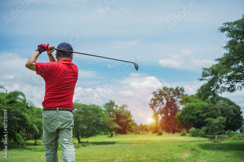 Plakat Mężczyzna bawić się golfa na polu golfowym w słońcu