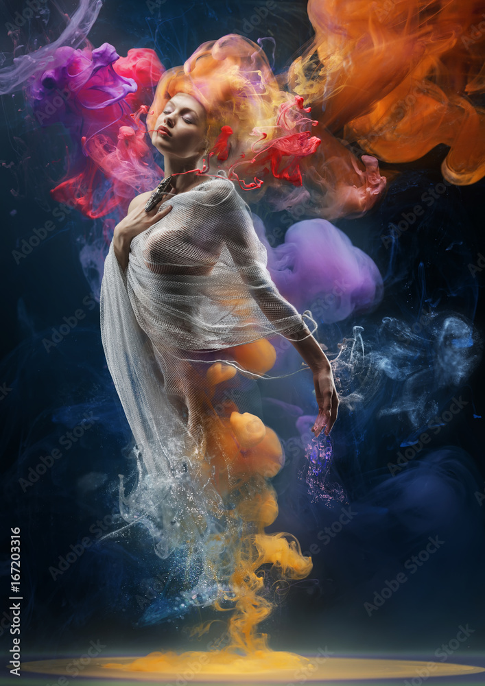 Fototapeta Fashion creative portrait of a blonde girl standing in clouds of watercolor paint