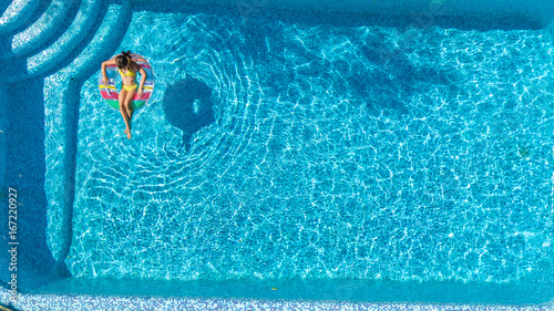 Aerial view of girl in swimming pool from above, kid swim on inflatable ring don Wallpaper Mural