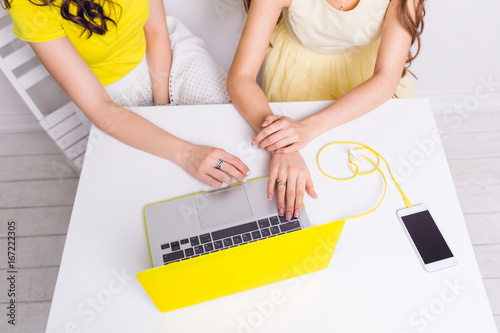 Close-up of a table with a laptop in yellow case and smartphone on yellow charger. Two girls sit behind table and hold their hands on the keyboards. They wear yellow clothes. Table is white.