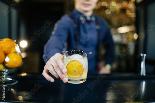 Fototapeta Bartender is making cocktail at bar.