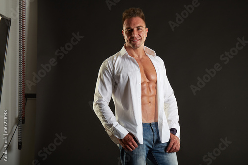 Fototapety, obrazy: Close up of sporty man posing in white shirt over black background