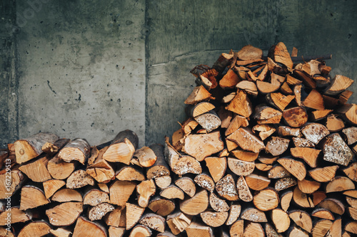 Poster Firewood texture chopped logs for winter fire. Pile of firewood against old wooden fence