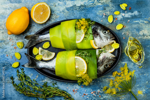 Fotografie, Obraz  Dorado wrapped in leek in baking form ready to cooking, preparation on rustic blue background with oil, herbs and spices