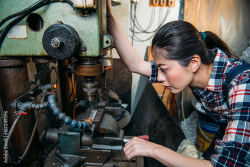 Valokuvatapetti factory female staff adjust industrial machines
