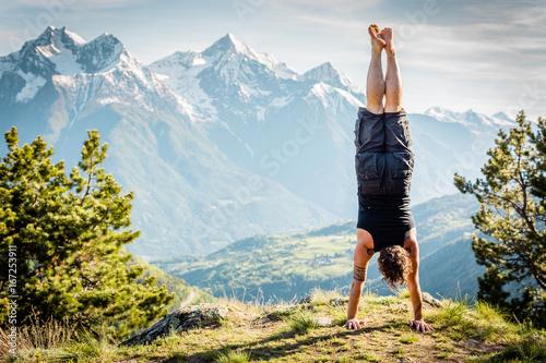 Fotografie, Tablou Ragazzo in verticale con panorama di montagna, a testa in giu