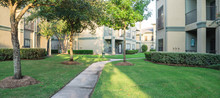 Clean Lawn And Tidy Oak Trees Along The Walk Path Through The Typical Apartment Complex Building In Suburban Area At Humble, Texas, US. Grassy Backyard, Sunset Warm Light. Panorama.