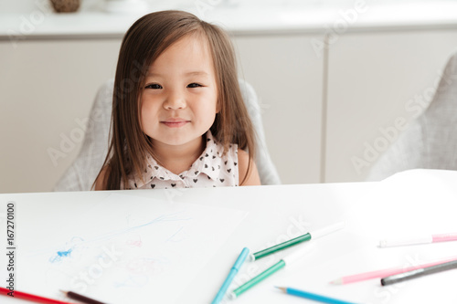 Little Cute Asian Girl At Home Indoors Drawing With Pencils