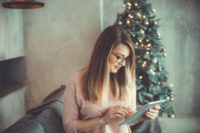 Young Woman Is Shopping With Tablet. Christmas Tree On Background In Loft Apartment. Christmas Time. Internet Shopping