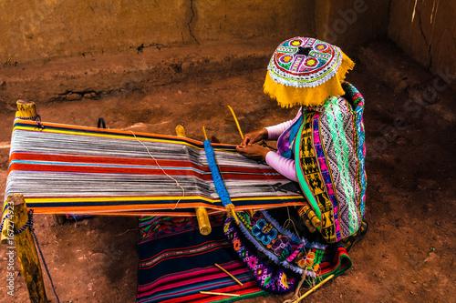 Fotobehang Zuid-Amerika land Peruvian woman weaving colorful alpaca wool, using ancient techniques