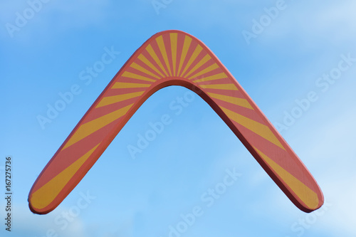 Photo Wooden australian boomerang in flight against of pure white clouds and blue sky