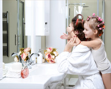 Young Mother And Daughter In Curlers In A Bath Room Happy Smiling Hide Eyes With Hands Skin Care