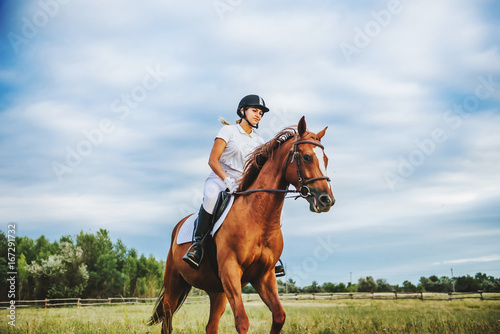 Photo Stands Horseback riding Girl jockey riding a horse