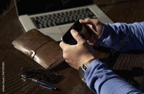 Fototapety, obrazy: Close-up of a man holding a phone at his workplace
