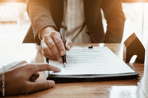 Close up of Business man pointing and signing agreement for buying house Canvas Print