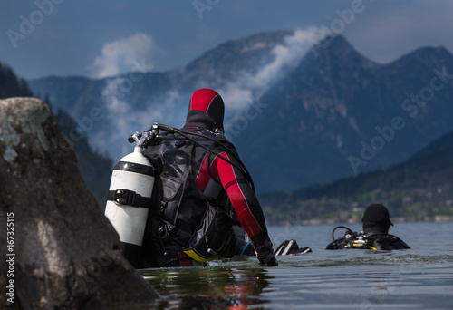 Divers entering water in mountain lake