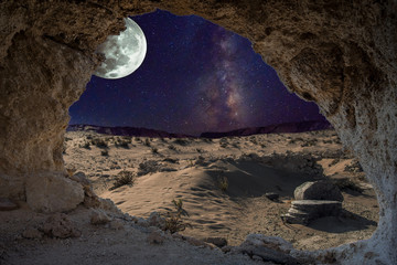 Fototapeta An unrealistic night landscape through a cave with milky, moon in eclipse, and desert with ruins of ancient columns.