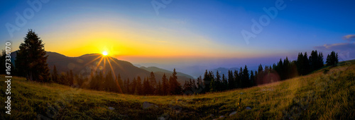 Fototapeta Panorama of a sunrise over a musty mountains and pine forest during late summer obraz