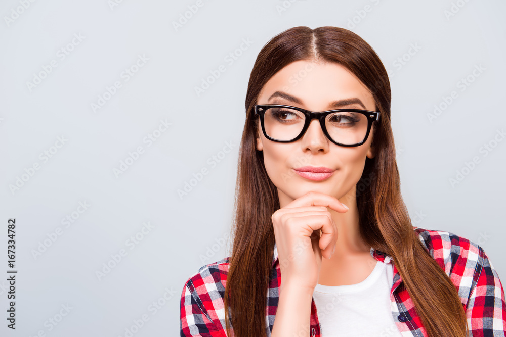 Fotografie, Tablou  Portrait of sceptic young freelancer brown haired lady, she is in glasses, casual wear, on pure light background