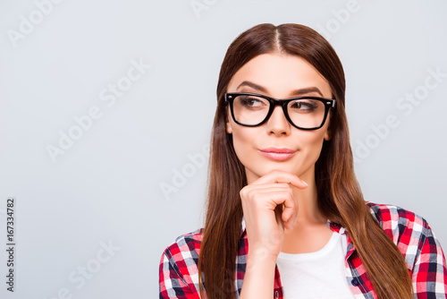 Valokuva  Portrait of sceptic young freelancer brown haired lady, she is in glasses, casual wear, on pure light background