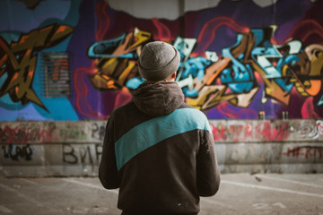 Graffiti artist standing near the wall