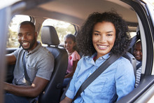 Young Black Family In A Car On A Road Trip Smiling To Camera