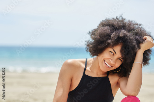pretty afro american woman on beach propping head on hand smiling