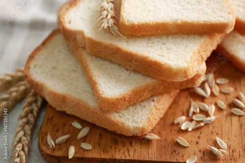 Delicious sliced bread on wooden cutting board