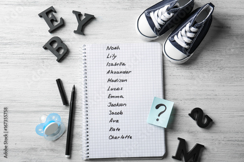 1b1fd9c0c3e2 Composition with list of baby names in notebook on wooden background ...
