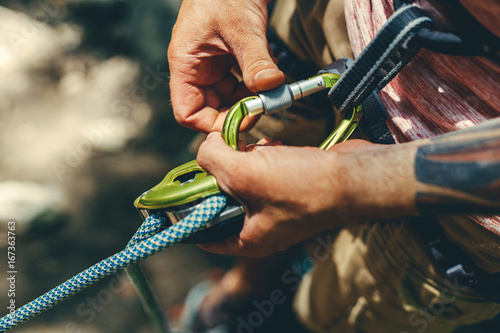Foto auf Leinwand Bergsteigen Unrecognizable Climber Man Wearing In Safety Harness Check Climbing Equipment Outdoor