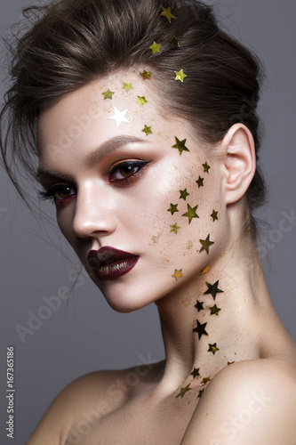 Close Up Portrait Of Beautiful Young Model With Evening Makeup And A Lot Of Golden Stars On Her Face Perfect Skin Volume Hairdo Trendy Colorful Smoky Eyes And Lips Art Makeup