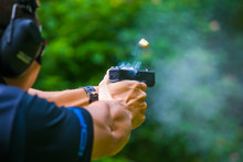 Shooting From A Pistol. Reloading The Gun. The Man Is Aiming At The Target. Shooting Range