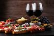 Italian antipasti wine snacks set. Cheese variety, Mediterranean olives, pickles, Prosciutto di Parma, tomatoes and wine in glasses. Spanish tapas